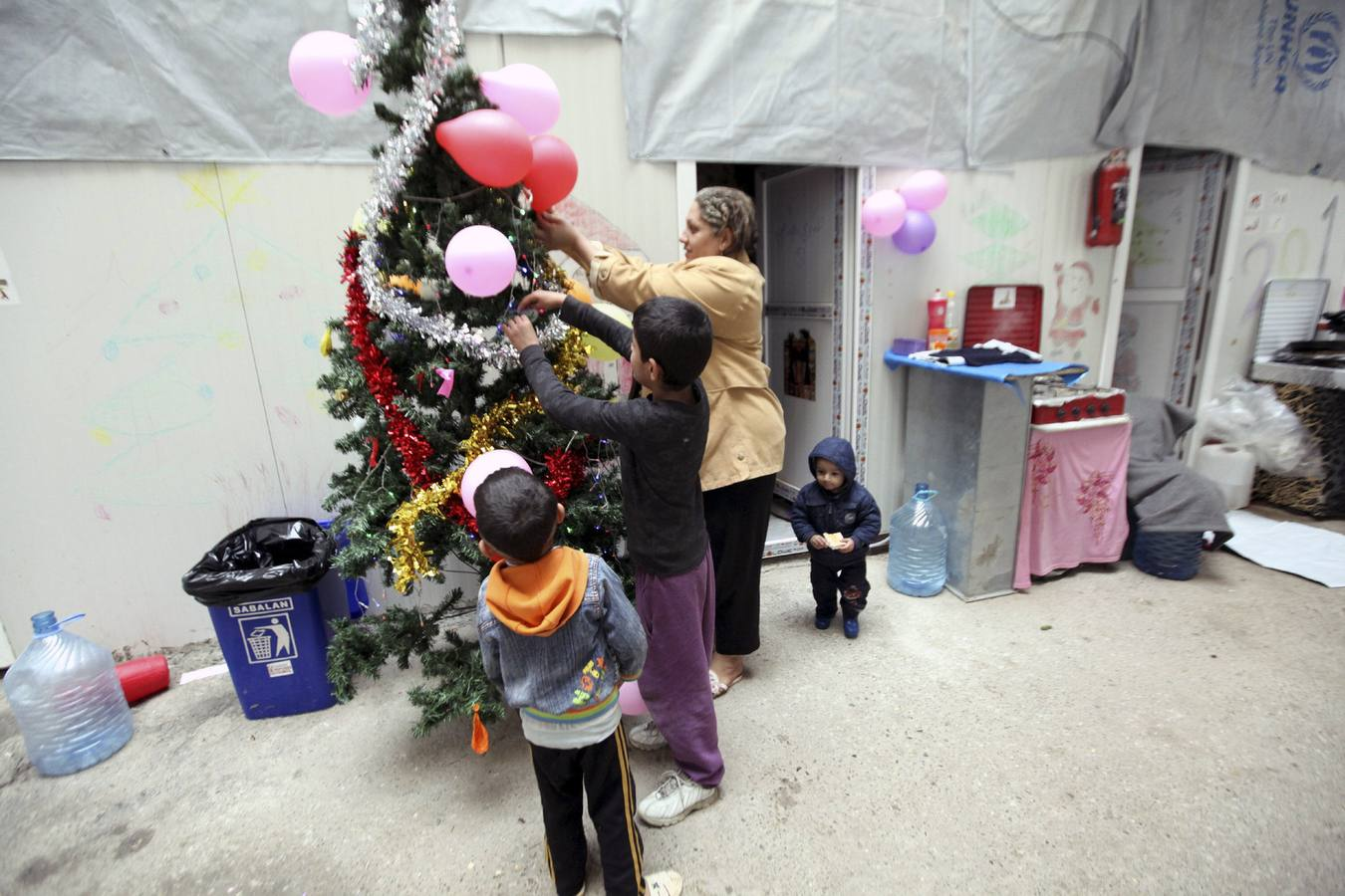 Displaced Iraqi Christian children who fled from Islamic State militants in Mosul, gather around a Christmas tree at a mall still under construction, used as a refugee camp in Arbil December 24, 2014. REUTERS/Azad Lashkari (IRAQ - Tags: SOCIETY CIVIL UNREST)